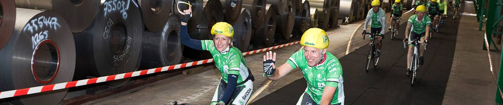 Radfahrer durchfahren das Hagener Werk von Waelzholz im Rahmen des Benefiz-Events Tour der Hoffnung.